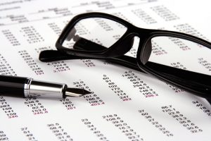 A Financial statement with eyeglasses and fountain pen.