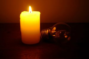 Burning candle and lamp on desktop in darkness. Troubles with electricy after storm