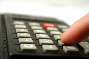 Close up of fingertip on the the keyboard of a calculator.