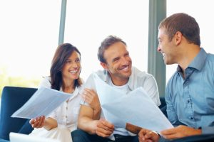 Smiling couple going over documents with consultant