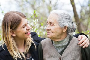Happy elderly woman with carer outdoor – springtime