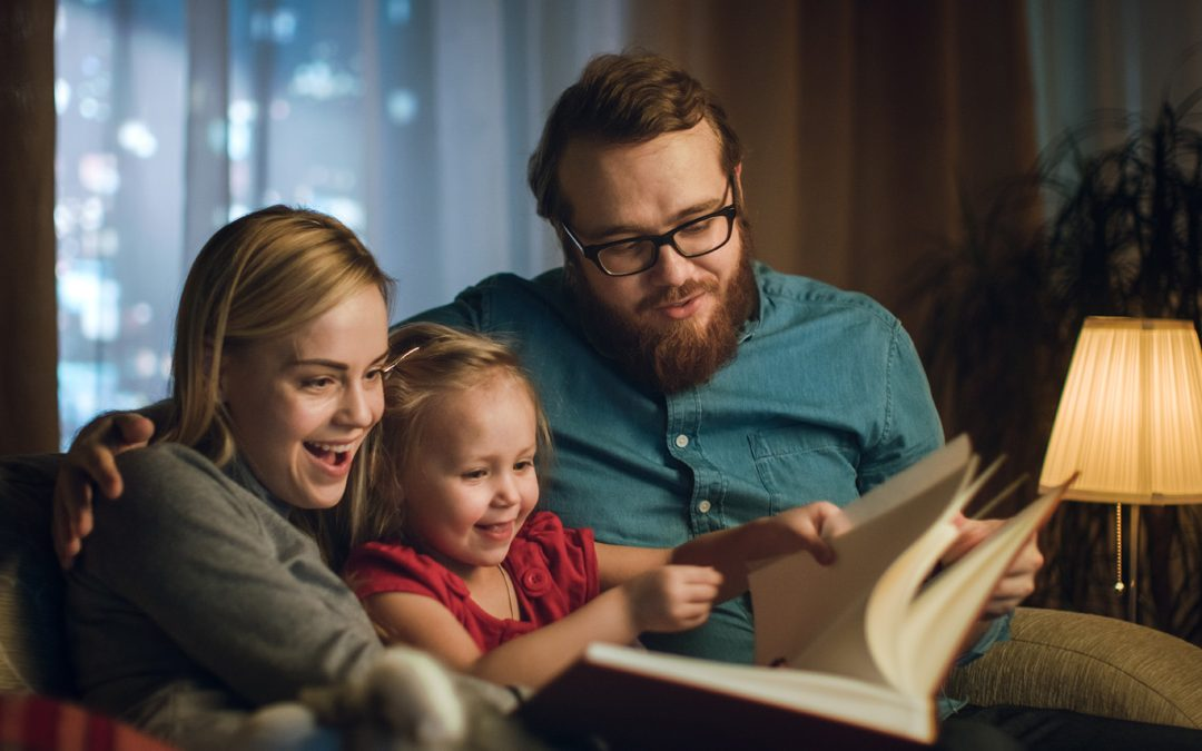 Family in warm living room reading a book