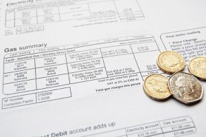 London, UK – January 13, 2011: close up of utility bill and coins for payment. The recent recession has had a big impact on households budgeting domestic bills.