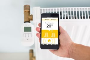 Person's Hand Adjusting Temperature Of Digital Smart Thermostat Using Mobile Phone App At Home