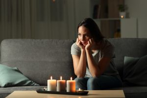 woman during a blackout in the night sitting on a couch in the living room at home