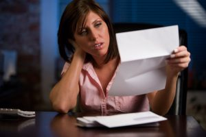 Young woman is frustrated going through correspondence